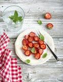 Υγιές ελαφρύ πρόχειρο φαγητό προγευμάτων Φέτες φραουλών με τη ζάχαρη, βασιλικός, μέντα για το επιδόρπιο σε ένα ξύλινο υπόβαθρο Στοκ φωτογραφία με δικαίωμα ελεύθερης χρήσης