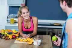 Υγιές ζεύγος που μιλά και που κρατά τα φρούτα Στοκ Φωτογραφίες