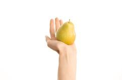 Υγιές θέμα κατανάλωσης και διατροφής: Ανθρώπινο χέρι που κρατά το κίτρινο αχλάδι απομονωμένο σε ένα άσπρο υπόβαθρο στο στούντιο,  Στοκ Φωτογραφίες