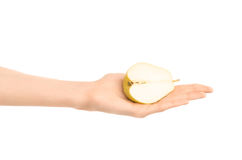 Υγιές θέμα κατανάλωσης και διατροφής: Το ανθρώπινο χέρι κρατά το μισό από το αχλάδι απομονωμένο σε ένα άσπρο υπόβαθρο στο στούντι Στοκ φωτογραφία με δικαίωμα ελεύθερης χρήσης