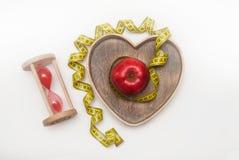 Υγιές καθεστώς τροφίμων διατροφής και ικανότητας: Ρολόι γυαλιού και η κόκκινη ώριμη Apple στο ξύλινο κιβώτιο μορφής καρδιών, που  Στοκ εικόνα με δικαίωμα ελεύθερης χρήσης