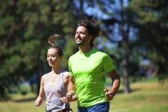 Υγιές, κατάλληλο και αθλητικό ζεύγος που τρέχει στο πάρκο Στοκ Φωτογραφίες