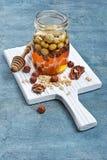 Υγιές μίγμα του φυσικού μελιού με τα διαφορετικά καρύδια σε ένα βάζο στο λευκό πίνακα στοκ εικόνες