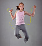 Υγιές νέο μυϊκό πηδώντας σχοινί έφηβη στο στούντιο Παιδί που ασκεί με το άλμα υψηλό στο γκρίζο υπόβαθρο Στοκ Εικόνες