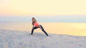 Υγιές, νέο όμορφο γυναικών, τέντωμα, γιόγκα άσκησης στην παραλία θάλασσας, στην ανατολή, κάνει τις ασκήσεις για απόθεμα βίντεο