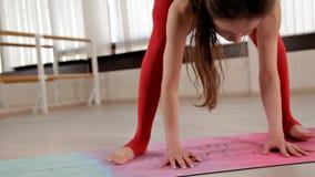 Υγιές νέο όμορφο κορίτσι στο κόκκινο κοστούμι που κάνει τη συνεδρίαση άσκησης στον τάπητα στο πάτωμα στο δωμάτιο με το φως της ημ απόθεμα βίντεο