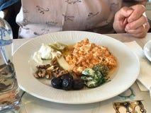 Υγιές πιάτο προγευμάτων με τα ανακατωμένα αυγά, την ελιά, το ξύλο καρυδιάς, το γιαούρτι και το πικάντικο τυρί στοκ εικόνα