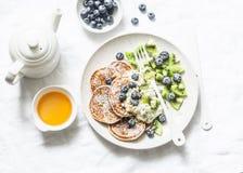 Υγιές πρόγευμα ή επιδόρπιο - ολόκληρες τηγανίτες σίτου με το ελληνικά γιαούρτι, τα βακκίνια, το ακτινίδιο, το μέλι και τα καρύδια στοκ φωτογραφίες με δικαίωμα ελεύθερης χρήσης