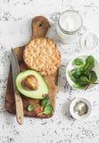 Υγιές πρόγευμα ή πρόχειρο φαγητό - αβοκάντο, ελληνικές γιαούρτι και κροτίδες σε ένα ελαφρύ υπόβαθρο, τοπ άποψη υγιής τρόπος ζωής  Στοκ Εικόνες