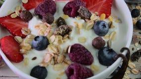 Υγιές πρόγευμα, δημητριακά με το γιαούρτι, φράουλες, βακκίνια, σμέουρα και muesli στο ξύλινο αγροτικό υπόβαθρο απόθεμα βίντεο
