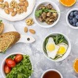 Υγιές πρόγευμα με τα τηγανισμένα αυγά, φρέσκο ψωμί, σαλάτα, μούρα, ντομάτες, καρύδια, φλυτζάνι ποτών, arugula, μανιτάρια στο α Στοκ Φωτογραφίες