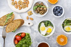 Υγιές πρόγευμα με τα τηγανισμένα αυγά, φρέσκο ψωμί, σαλάτα, μούρα, ντομάτες, καρύδια, φλυτζάνι ποτών, arugula, μανιτάρια στο α Στοκ Εικόνες