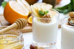 Υγιές πρόγευμα με το γιαούρτι στο γυαλί, το granola και τα φρούτα Στοκ Φωτογραφία