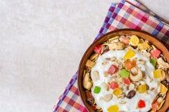 Υγιές πρόγευμα με το γιαούρτι, το muesli και τα γλασαρισμένα φρούτα στο κεραμικό κύπελλο στο υπόβαθρο πετρών Στοκ φωτογραφίες με δικαίωμα ελεύθερης χρήσης