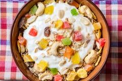 Υγιές πρόγευμα με το γιαούρτι, το muesli και τα γλασαρισμένα φρούτα στο κεραμικό κύπελλο στο υπόβαθρο πετρών Στοκ φωτογραφία με δικαίωμα ελεύθερης χρήσης