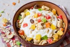 Υγιές πρόγευμα με το γιαούρτι, το muesli και τα γλασαρισμένα φρούτα στο κεραμικό κύπελλο στο υπόβαθρο πετρών Στοκ Φωτογραφία