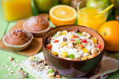 Υγιές πρόγευμα με το γιαούρτι, το muesli και τα γλασαρισμένα φρούτα στο κεραμικό κύπελλο στο πράσινο ξύλινο υπόβαθρο Στοκ φωτογραφία με δικαίωμα ελεύθερης χρήσης