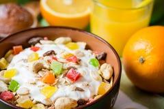 Υγιές πρόγευμα με το γιαούρτι, το muesli και τα γλασαρισμένα φρούτα στο κεραμικό κύπελλο στο πράσινο ξύλινο υπόβαθρο Στοκ Φωτογραφία