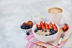 Υγιές πρόγευμα με oatmeal το κουάκερ, τα φρέσκους μούρα και τον καφέ στοκ εικόνες