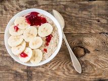 Υγιές πρόγευμα το πρωί - oatmeal με τις φέτες της μπανάνας Στοκ Εικόνες