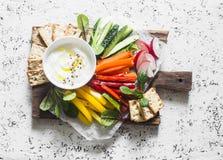 Υγιές πρόχειρο φαγητό - ακατέργαστες λαχανικά και σάλτσα γιαουρτιού σε έναν ξύλινο τέμνοντα πίνακα, σε ένα ελαφρύ υπόβαθρο, τη το Στοκ φωτογραφίες με δικαίωμα ελεύθερης χρήσης