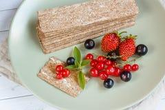 Υγιές πρόχειρο φαγητό από τις Wholegrain κροτίδες παξιμαδιών σίκαλης και τα φρέσκα μούρα στο ελαφρύ υπόβαθρο Στοκ Φωτογραφία