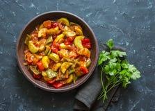 Υγιές χορτοφάγο μεσημεριανό γεύμα - που μαγειρεύεται, αργά λαχανικά κήπων Φυτικό Ratatouille Σε μια σκοτεινή ανασκόπηση Στοκ Εικόνες