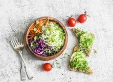 Υγιές χορτοφάγο πρόχειρο φαγητό άνοιξη - σαλάτα και σάντουιτς λάχανων με τα πράσινα αβοκάντο και μικροϋπολογιστών σε έναν ελαφρύ  Στοκ Εικόνες