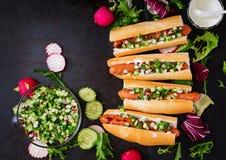 Υγιές χοτ-ντογκ που ντύνεται με το salsa γιαουρτιού και αγγουριών με τα ραδίκια Στοκ φωτογραφία με δικαίωμα ελεύθερης χρήσης
