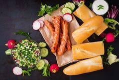 Υγιές χοτ-ντογκ που ντύνεται με το salsa γιαουρτιού και αγγουριών με τα ραδίκια Στοκ Εικόνες