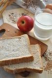 Υγιές ψωμί σίτου συστατικών με το ποτήρι του γάλακτος και της Apple Στοκ Εικόνες