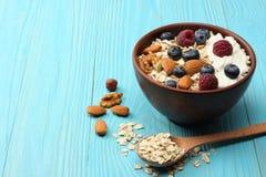 υγιές oatmeal, βακκίνια, σμέουρα και καρύδια προγευμάτων στον μπλε ξύλινο πίνακα Στοκ Εικόνα