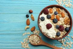 υγιές oatmeal, μέλι, βακκίνια, σμέουρα και καρύδια προγευμάτων στον μπλε ξύλινο πίνακα Τοπ άποψη με το διάστημα αντιγράφων Στοκ Εικόνα