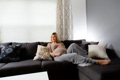 Υγιής έγκυος γυναίκα που βρίσκεται σε έναν καναπέ Στοκ φωτογραφία με δικαίωμα ελεύθερης χρήσης