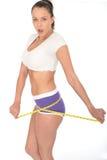 Υγιής έκπληκτη κατάλληλη νέα γυναίκα που ελέγχει την απώλεια βάρους της με ένα μέτρο ταινιών στοκ φωτογραφίες με δικαίωμα ελεύθερης χρήσης