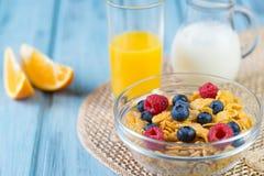 Υγιής έννοια προγευμάτων - δημητριακά με τα μούρα, το χυμό από πορτοκάλι, τις πορτοκαλιά φέτες και το γάλα Στοκ Εικόνες