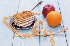 Υγιής έννοια τροφίμων, κομμάτι του κέικ στον ξύλινο πίνακα και μέτρηση της ταινίας Στοκ Φωτογραφία