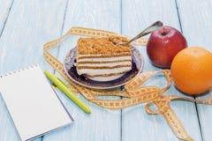 Υγιής έννοια τροφίμων, κομμάτι του κέικ στον ξύλινο πίνακα και μέτρηση της ταινίας με το σημειωματάριο και τη μάνδρα Στοκ Φωτογραφίες