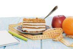Υγιής έννοια τροφίμων, κομμάτι του κέικ στον ξύλινο πίνακα και μέτρηση της ταινίας με το σημειωματάριο και τη μάνδρα Στοκ Εικόνες