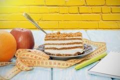 Υγιής έννοια τροφίμων, κομμάτι του κέικ στον ξύλινο πίνακα και μέτρηση της ταινίας με το σημειωματάριο και τη μάνδρα Στοκ Εικόνα
