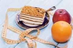 Υγιής έννοια τροφίμων, κομμάτι του κέικ στον ξύλινο πίνακα και μέτρηση της ταινίας Στοκ εικόνα με δικαίωμα ελεύθερης χρήσης
