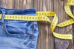 Υγιής έννοια τρόπου ζωής και διατροφής Τζιν παντελόνι με μια μετρώντας ταινία αντί μιας ζώνης Στοκ Φωτογραφία