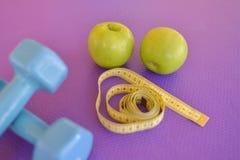 Υγιής έννοια τρόπου ζωής - πράσινο μήλο με τους αλτήρες και την κίτρινη μετρώντας ταινία Στοκ Φωτογραφία