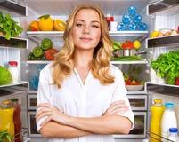 Υγιής γυναίκα κοντά στο ανοικτό ψυγείο στοκ εικόνες