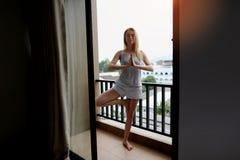 Υγιής γυναίκα που κάνει την ενέργεια γιόγκας στο χρόνο ανατολής ξενοδοχείων μπαλκονιών στοκ εικόνες