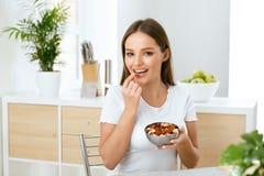 υγιής διατροφή Όμορφη νέα γυναίκα που τρώει τα καρύδια στοκ φωτογραφίες