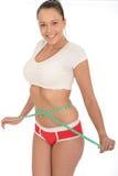 Υγιής ευτυχής ευτυχής νέα γυναίκα που ελέγχει την απώλεια βάρους της με ένα μέτρο ταινιών στοκ εικόνες με δικαίωμα ελεύθερης χρήσης