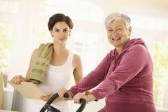Υγιής ηλικιωμένη γυναίκα στο ποδήλατο άσκησης Στοκ εικόνα με δικαίωμα ελεύθερης χρήσης