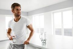 υγιής διατροφή Γυαλί κατανάλωσης ατόμων του γλυκού νερού το πρωί στοκ φωτογραφία