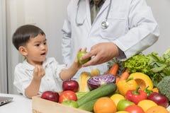 Υγιής και έννοια διατροφής Παιδί που μαθαίνει για τη διατροφή με το γιατρό για να επιλέξει την κατανάλωση των φρέσκων φρούτων και στοκ φωτογραφία με δικαίωμα ελεύθερης χρήσης